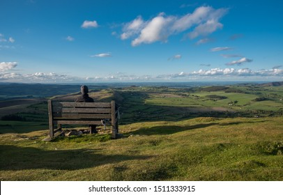 A hiker sits on a bench looking out over the Mid Wales Countryside. Corndon Hill, Powys, Wales.