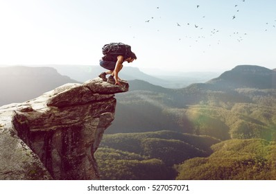 Hiker sits on a cliff