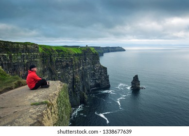 Hiker sitting at the cliffs of Moher located at the edge of the Burren region in County Clare, Ireland.