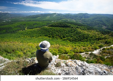 Hiker sitting on cliff edge and enjoying scenic view.