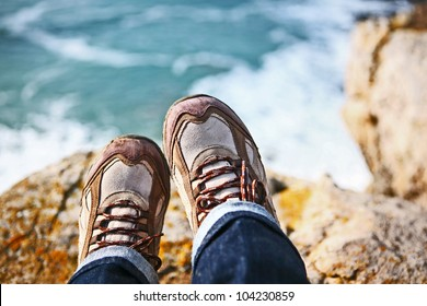 Hiker Sitting on Edge of Cliff Wearing Hiking Boots Overlooking the Ocean Water on a Sunny Day