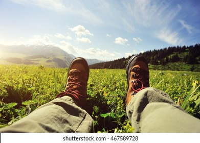 hiker sitting on a grass mountain top with first person perspective view