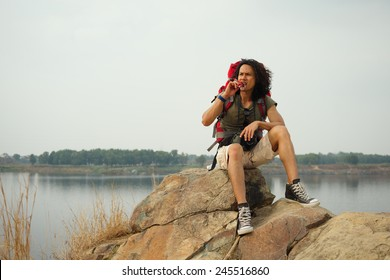 Hiker sitting on mountain and eating a chocolate bar