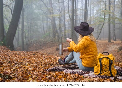 Hiker sitting on picnic blanket and drinking hot drink in autumn forest. Woman resting in nature during hike