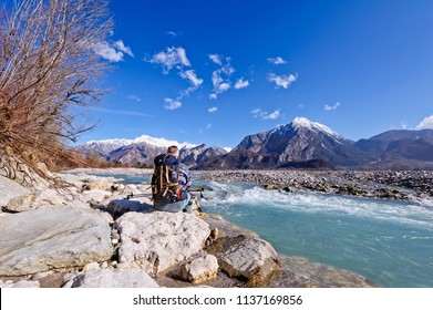 Hiker sitting on river shore over the rocks, looking the mountains landscape.Alps,Italy,Friuli.