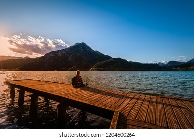 Hiker sitting on the wooden pier. Tramper looking the landscape at sunset on lake.