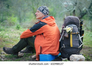 Hiker sitting and resting near two backpacks. Relaxed man with wild flowers while traveling in the mountains. Romantic travel destinations