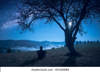 Hiker sitting under the big tree in a night mountain valley and enjoy milky way in a starry sky.