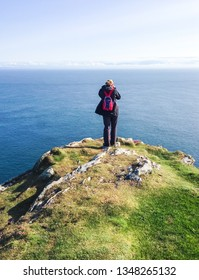 A hiker with a small red backpack stands on the edge of a cliff overlooking the ocean on a sunny day. Photographed on the tip of the Oa Peninsula on the island of Islay in Scotland.