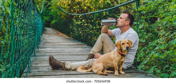 Hiker with small yellow dog resting on the wooden suspension bridge in the forest and drinking water