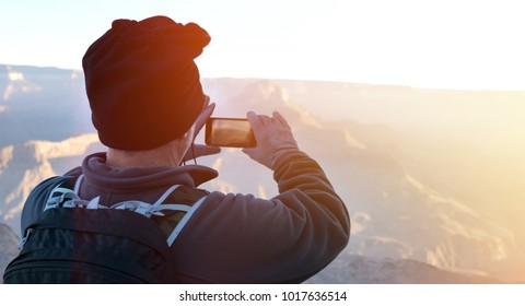 Hiker with smartphone taking morning panormic pictures while travelling at the Grand Canyon with sun flare on the side. Making a living as digital Nomad taking stock images.