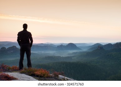 Hiker in sportswear stand on the peak of sandstone rock in rock empires park and watching over the misty and foggy morning valley to Sun. Beautiful moment the miracle of nature