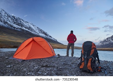 Hiker stand at the camping near orange tent and backpack in the mountains during springtime. Backpacker looking into the distance