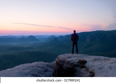 Hiker stand on the sharp corner of sandstone rock in rock empires park and watching over the misty and foggy morning valley to Sun