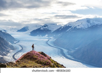 Hiker standing against famous Salmon glacier near Stewart, Canada - Alaska border.