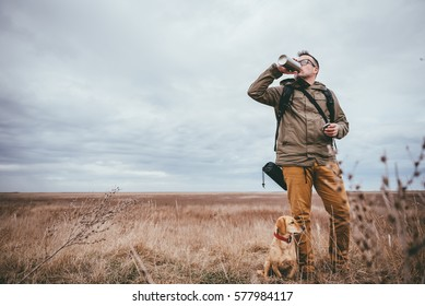 Hiker standing in grassland with a dog and drinking water