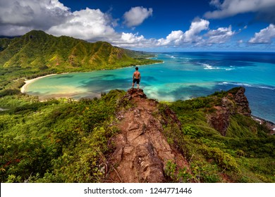 Hiker standing majestically on top of a cliff on the Pu'u Manama trail in Hawaii