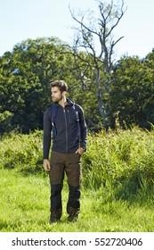 Hiker standing in meadow, looking away