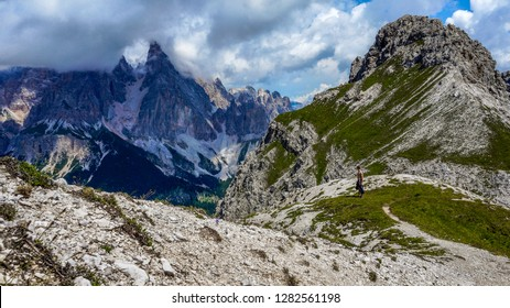 Hiker standing in the mountains and enjoying the view of Cristallo group. Trekking from Cortina d'Ampezzo to Lake Sorapis - Dolomite Alps, Belluno,Veneto, Italy