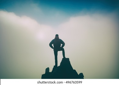 Hiker standing on a cliffs edge. The top of the mountain. Colorful clouds in a light of sunrise.