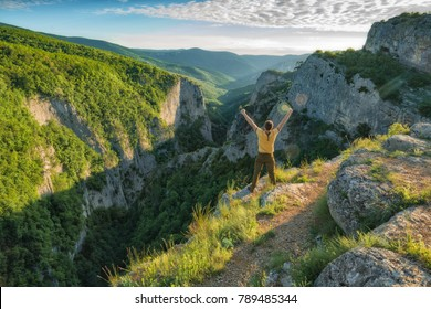 Hiker standing on a cliffs edge above the mountain canyon of Crimea at the sunset light.