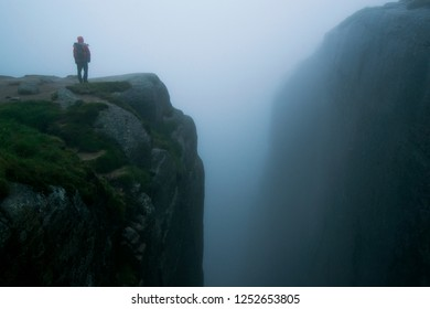 Hiker standing on the edge of a cliff in foggy weather in Norway on the way to the kjerag