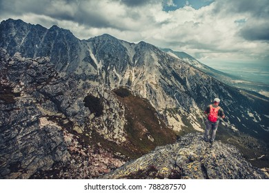 A hiker is standing on the edge of the precipice in the Tatra Mountains, Slovakia. Outdoor extreme activity. Unforgettable magnificent panoramic view. Serenity of wild virgin nature.