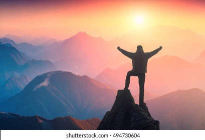 Hiker standing on a peak of mountain with raised hands and rejoices sunrise above the misty valley.