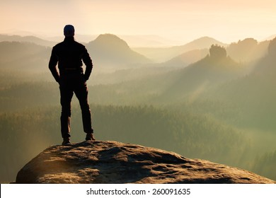 Hiker is standing on peak of sandstone rock in rock empires park and watching over misty and foggy morning valley to Sun. Beautiful moment miracle of nature. Hiker silhouette watching. Person standing