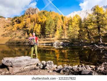 Hiker standing on rock admire the lake and the autumn colors of landscape. Colourful autumn morning in mountain lake. Colorful autumn landscape. Lake of Borfaglia, Friuli, Italy.