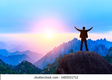 Hiker is standing on a rock with raised hands and enjoying sunrise