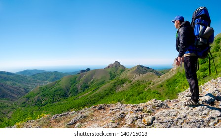 Hiker standing on a stone ridge and enjoys landscape