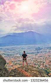 Hiker standing on top of mountain enjoying sunrise and looking at a beautiful landscape cityscape. Monastery Meteora Kalambaka in Greece Europe. Aim top business thinking concept. Wanderlust adventure