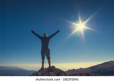 Hiker standing on top of a mountain with raised hands and enjoying landscape.
