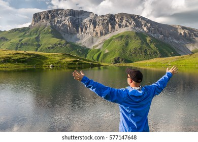 Hiker standing with raised hands near the beautiful mountain lake and enjoying view. Concept of extreme sport and active life
