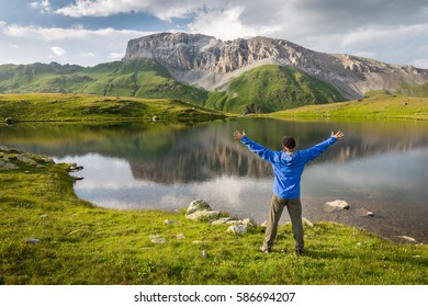 Hiker standing with raised hands near the beautiful mountain lake and looking at rocky mountain