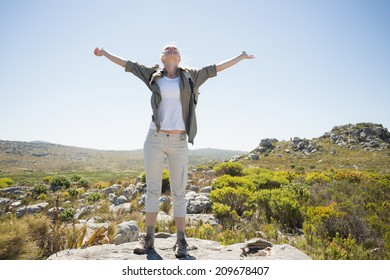 Hiker standing at the summit with her arms out on a sunny day