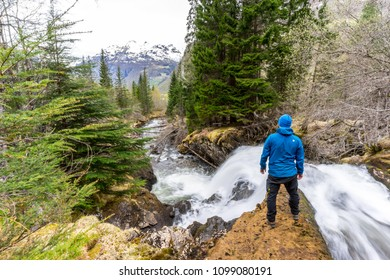 Hiker standing at a waterfall in forest above Geiranger village in Norway