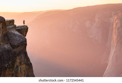 A hiker stands at the edge of a cliff at Taft Point overlooking El Capitan in Yosemite National Park, California.