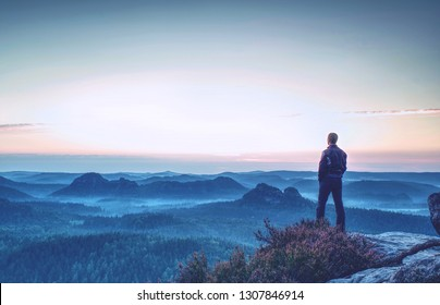 Hiker stands and enjoys valley view from hilly viewpoint. Hiker reached top of the mountain and watching sunset.