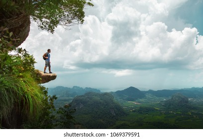Hiker stay on a cliff,enjoy view of nature landscape