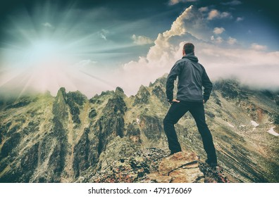 Hiker stays on a rocky ridge and enjoy beautiful sunrise in a mountain valley. Caucasian, Georgia, Swaneti region.