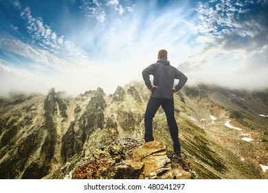 Hiker stays on a rocky ridge and enjoy beautiful sunrise in a mountain valley. Caucasian, Georgia, Svaneti region.