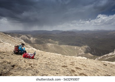 A hiker surveying his surroundings as a storm rolls in in Western China.