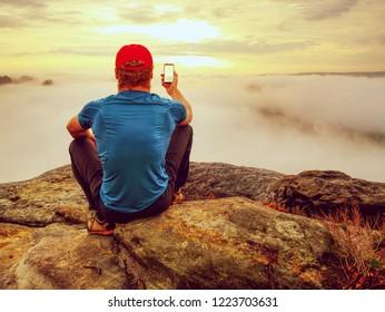 Hiker takes selfie photo, fall nature adventure. Man sit on stone on mountain sumit  Daybreak horizon above milky fog.