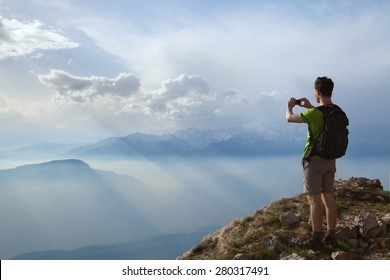 hiker taking photo of beautiful mountain landscape with mobile phone