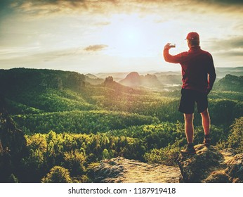 Hiker is taking photo by smart phone on the peak of mountain. Man in red t-shirt and shorts takes photos with smart phone on peak of rock empire. Dreamy fogy landscape