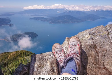 hiker taking rest on mountaintop overlooking water and islands in distance with well worn hiking boots in foreground