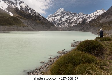 A hiker taking in the view of snow capped Mount Cook with Hooker Lake in the foreground and the Hooker Glacier in the middle ground. Aoraki/Mount Cook National Park, Canterbury, New Zealand.