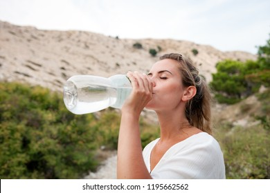 Hiker tired woman on trekking trail drinking water, travel and fit lifestyle concept